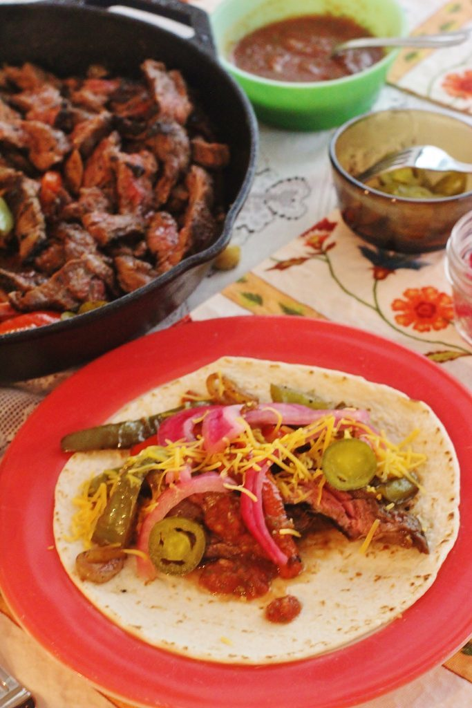 Beef Fajitas. Marinated skirt steak, onions and peppers. Served on flour tortillas with toppings.