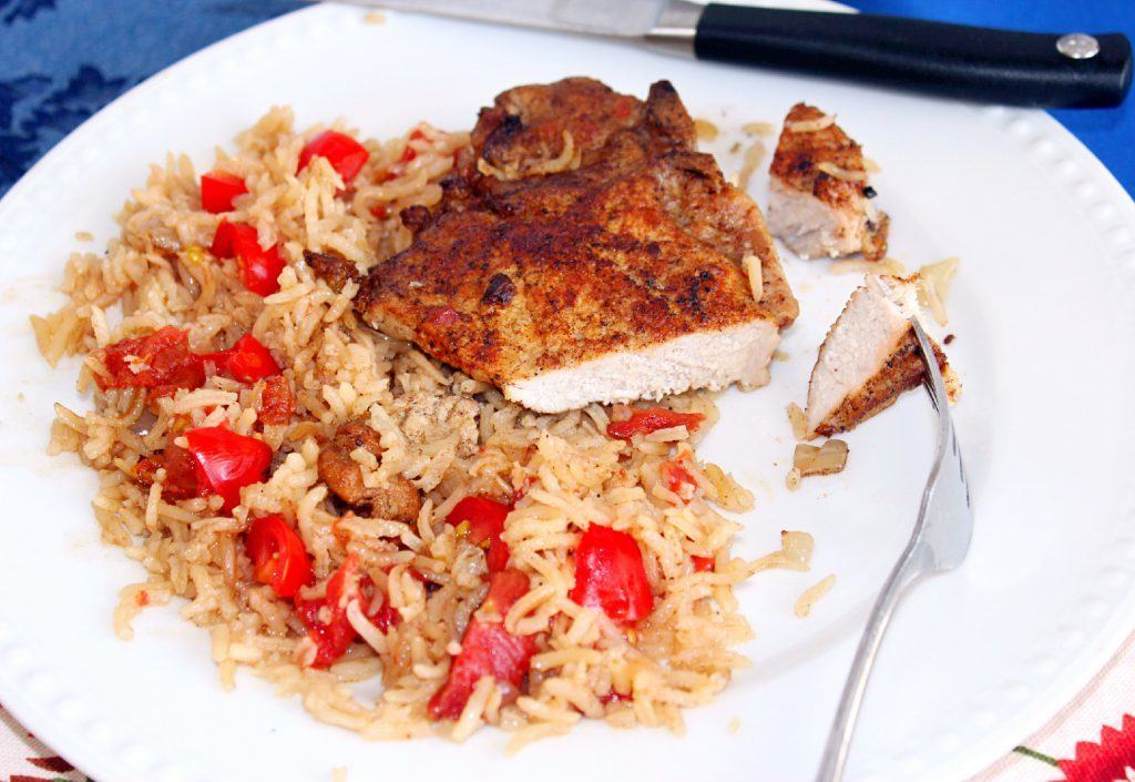 Baked Pork Chops with Tomatoes and Rice with pork chops on a plate.