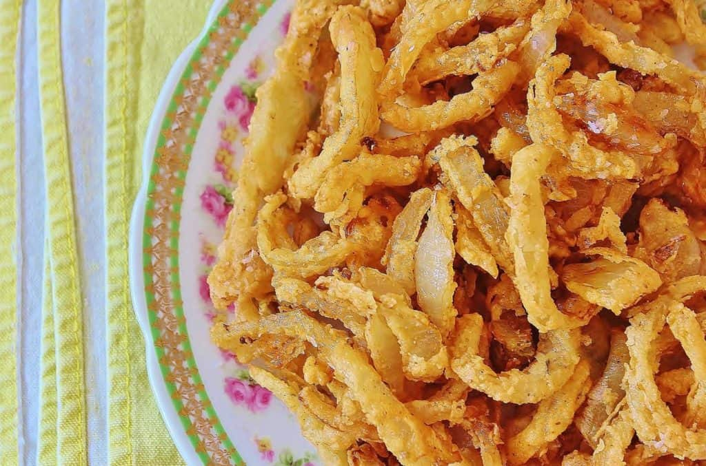 Cajun Crispy Fried Onions. Thinly sliced onions lightly coated with a buttermilk and seasoned flour batter. Makes fried onions easy and with less mess to clean up. #cajun #fried #onion #rings #southernfood