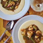 Shrimp and Grits. Gravy of sauteed onions and peppers, ham and shrimp served over creamy, cheesy grits.