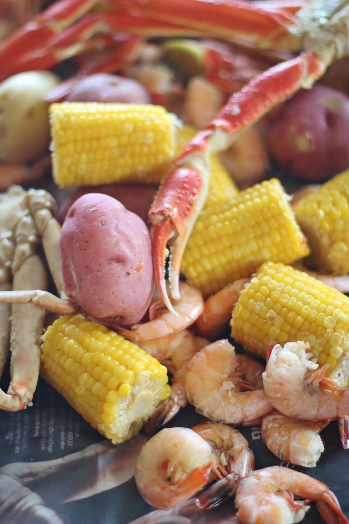 Shrimp and Crab boil with potatoes and corn on table.