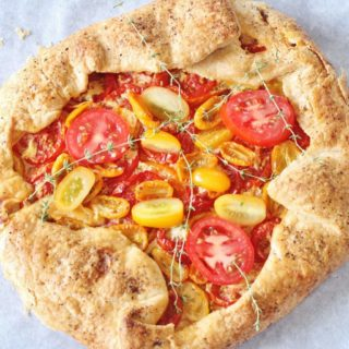 Rustic Tomato Pie. A free-formed butter crust with an herb goat cheese filling topped with fresh sliced tomatoes.
