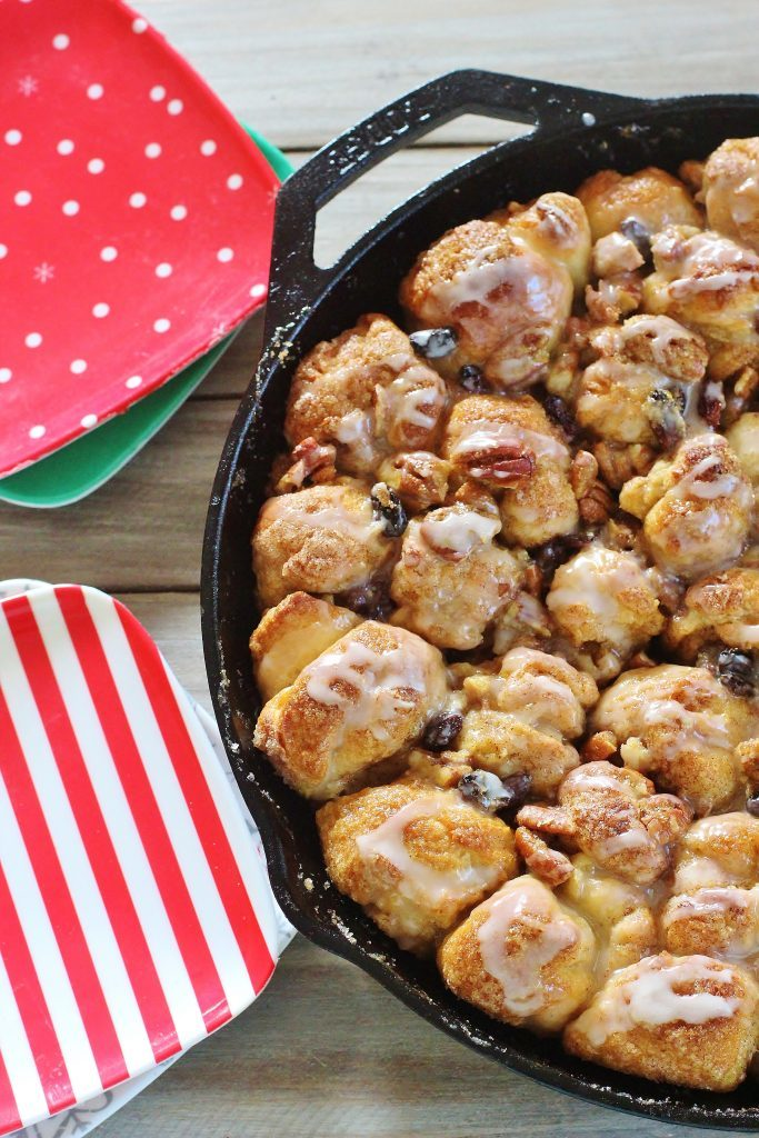Skillet Monkey Bread. Bits of yeast dough coated in butter and cinnamon sugar, baked with raisins and pecans in a caramel-y topping and finished with buttermilk glaze.