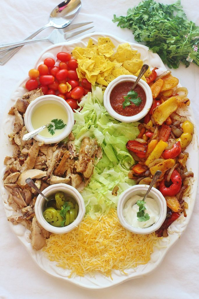 Chicken Fajita Salad. Marinated and roasted chicken thighs with seasoned peppers and onions served on a bed of lettuce with traditional fajita toppings.