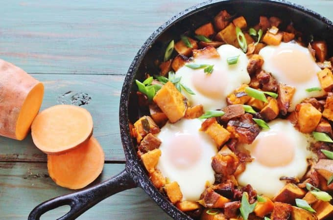 """Sweet Potato Bacon Hash with Baked Eggs. A skillet meal of sweet potatoes, sweet onions, bacon and eggs. From the cookbook """"Sweet Potato Love"""" by Jackie Garvin."""