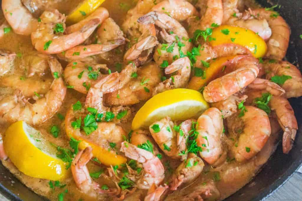 shrimp in a cast iron skillet in buttery broth