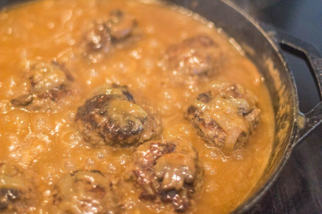 Southern-Style Hamburger Steaks with Onion Mushroom Gravy in skillet.