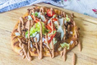 Grilled Flatbread Taco Pizza with Creamy Taco Sauce. Made with pre-packaged naan bread, taco seasoned ground beef and your favorite taco toppings. Topped with an easy and creamy homemade taco sauce.