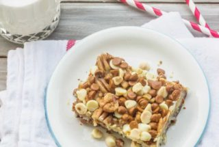 Gingerbread Magic Cookie Bars is a variation of the original Magic Cookie Bars from Eagle Brand Sweetened Condensed Milk.  Gingersnap cookies and orange juice form a  crust that's reminiscent of gingerbread cake. The layers of coconut, white chocolate, cinnamon chips, and toffee chips add a delightful spin to the classic recipe.