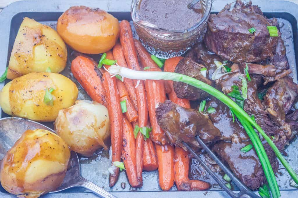pot roast with vegetables and gravy on a platter.