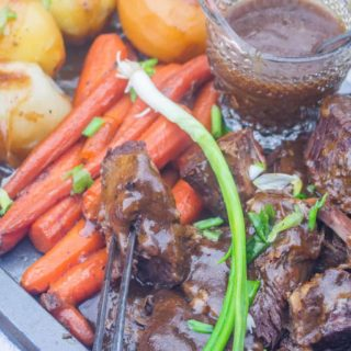 pot roast with vegetables and gravy on a platter