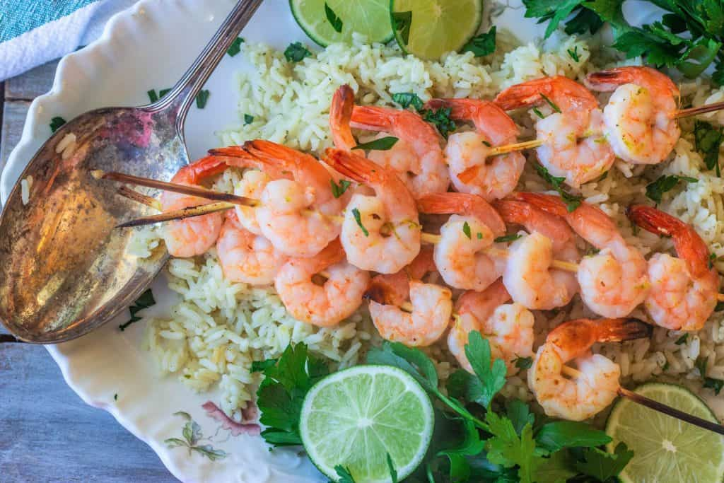 skewered marinated shrimp with cilantro lime rice on a platter