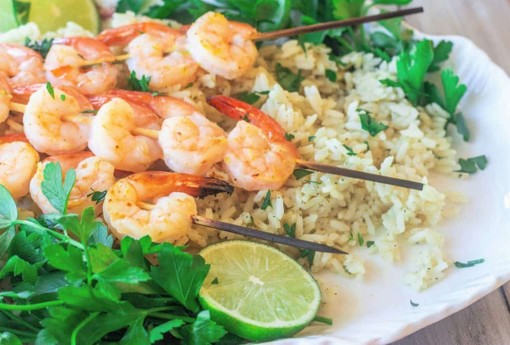 skewered shrimp with cilantro lime rice on a platter