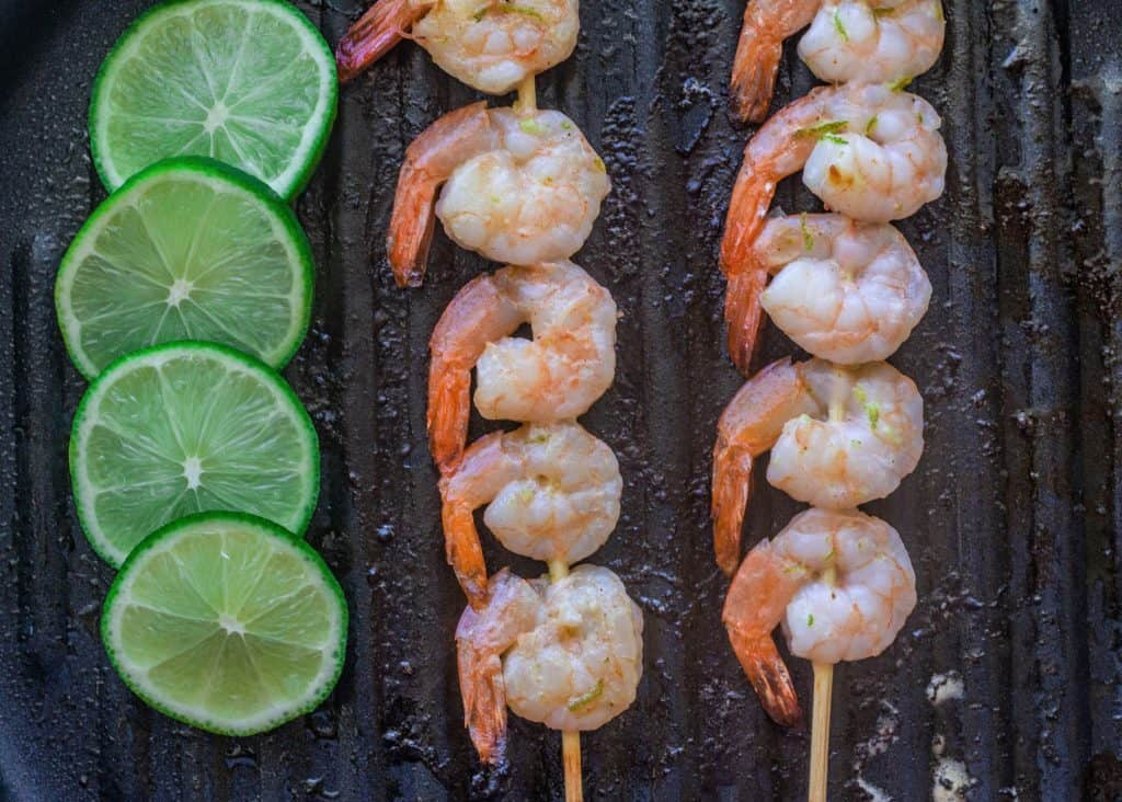 skewered shrimp and limes on a grill pan