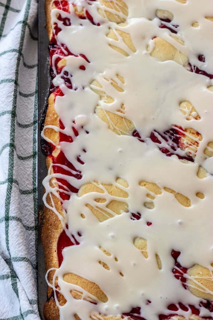 Cherry pie bars with buttermilk glaze in baking sheet.