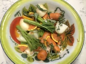 Fruits, vegetables, and herbs in an enamel bowl.