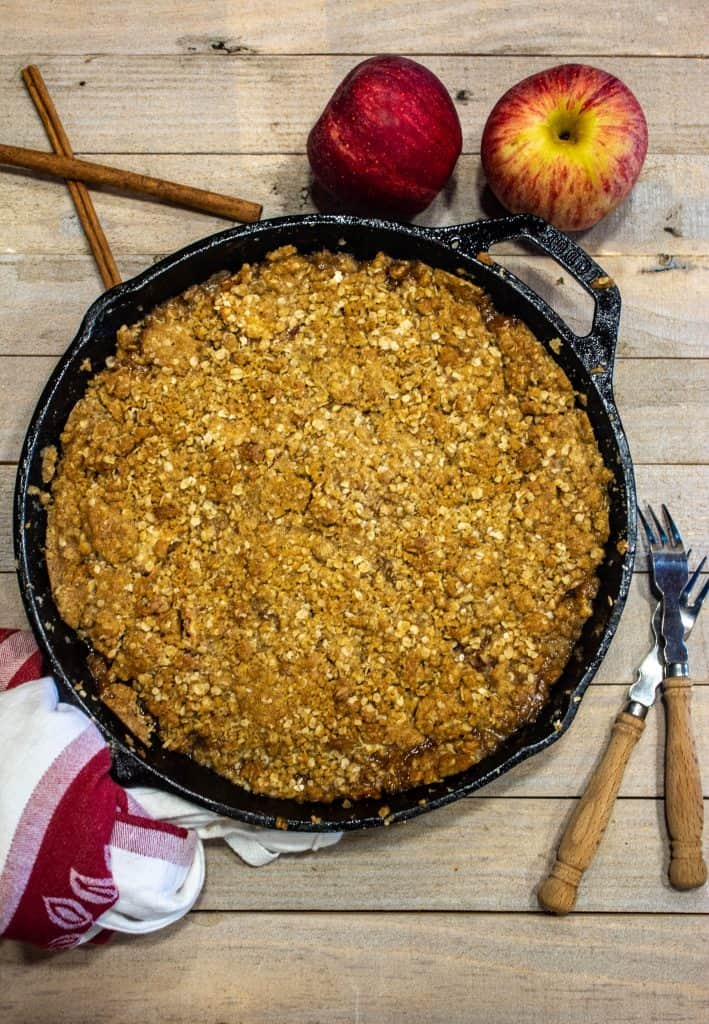 apple crisp in a cast iron skillet with cinnamon sticks and whole apples around the skillet