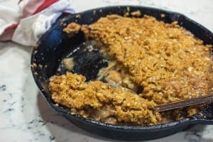 apple crisp in a cast iron skillet with a serving spoon